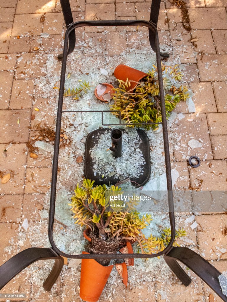 Broken tempered glass patio table upside down with damaged potted plants after a wind storm : Stock Photo