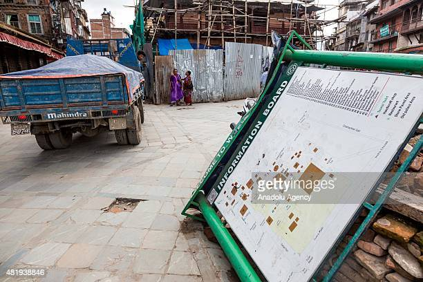 Broken tourist information boards rests on its side against debris from one of the destroyed temples in Durbar square in Kathmandu on July 25, 2015....