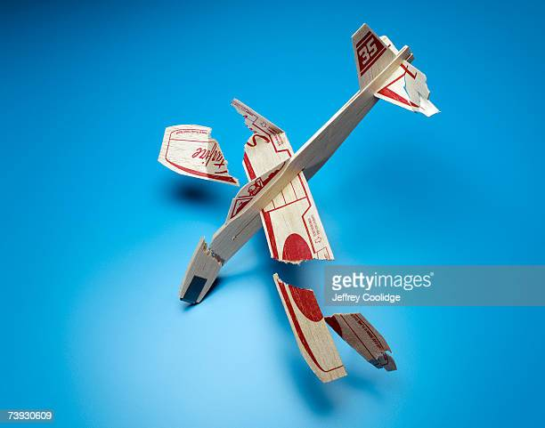 Broken toy airplane on blue background, studio shot