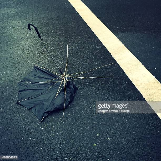 Broken Umbrella Abandoned In Middle Of Wet Road On Rainy Day