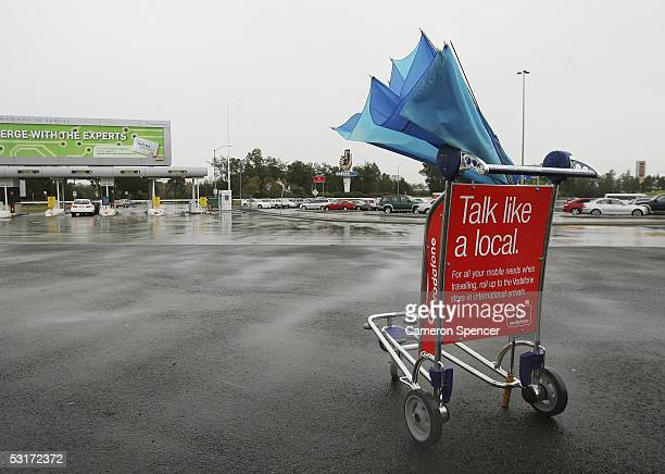 Broken umbrella is left in a trolley at Sydney Airport as heavy rain continues to fall across Sydney June 30 2005 in Sydney Australia The consistent...