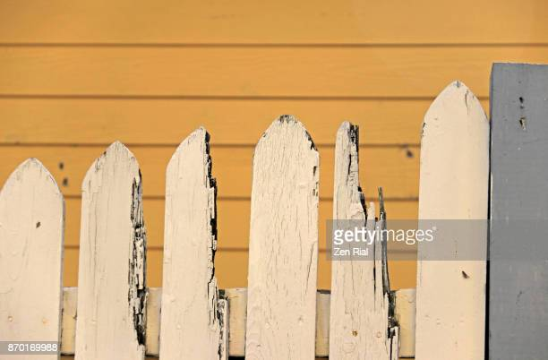 Broken white picket fence against yellow background