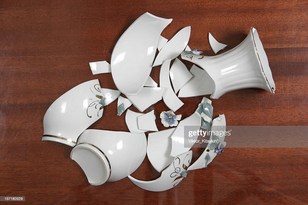 Broken white porcelain vase on wooden floor : Stock Photo