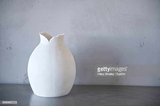 Broken White Vase Against Wall
