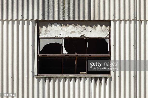 Broken window in a wall of corrugated steel