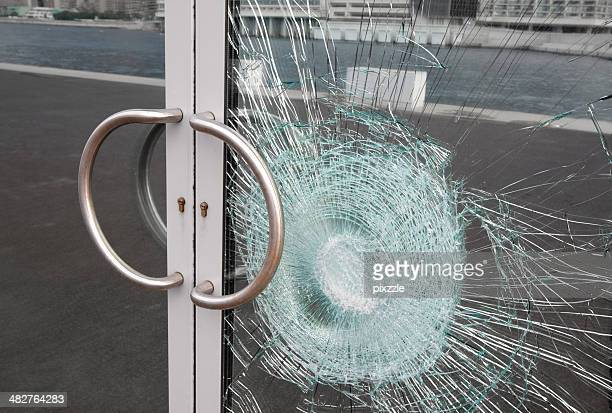 Broken window on business glass door shattered by vandalism