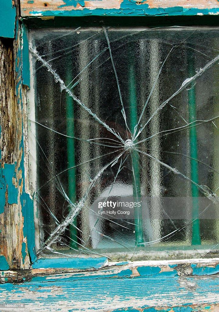 Broken window with blue peeling paint on frame : Stock Photo