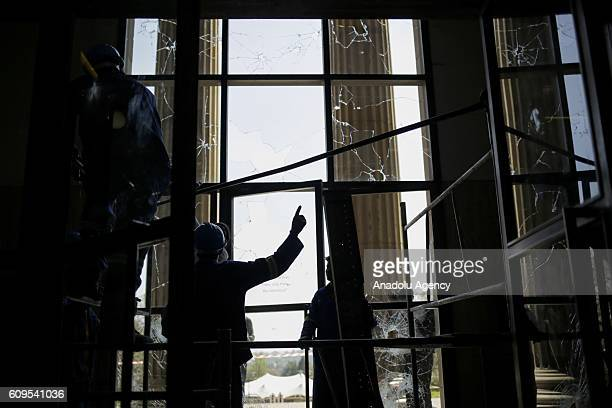 Broken windows of a building is seen as group of students gather to protest after South African Minister of Higher Education and Training Blade...