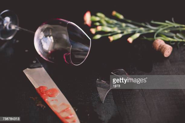 Broken wine glass, flowers and a bloody knife