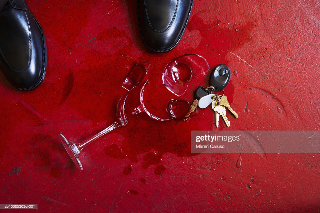 Broken wine glass splattered on floor, beside set of keys and man's shoes : Foto stock