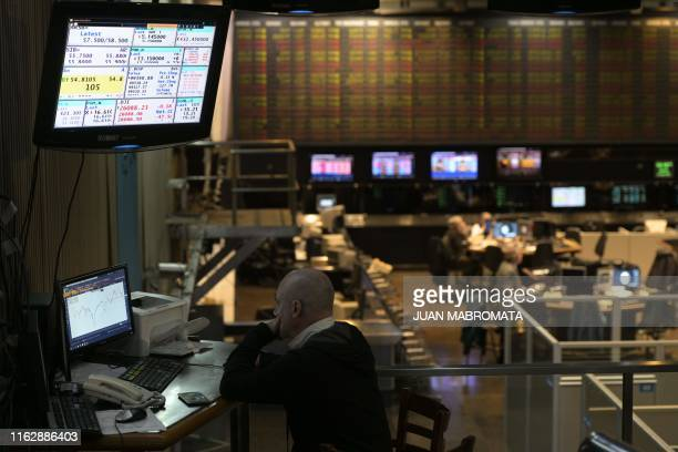 A broker looks at a screen at the Buenos Aires Stock Exchange in the financial district of Buenos Aires on August 20 2019 after Argentina's President...