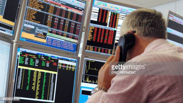 A broker makes a phone call in front of screens in an office of the French investment company Aurel BGC in Paris on September 12 2011 The French...