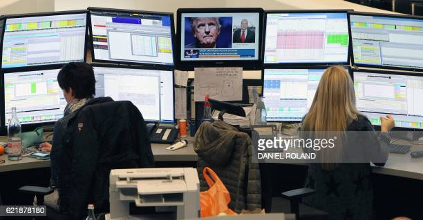 Brokers are pictured at the stock exchange in Frankfurt Germany on November 9 2016 as the Tv screens shows the results of presidential elections in...