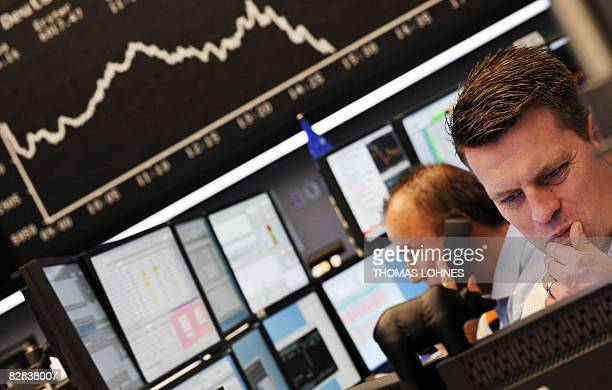 Brokers look at their screens at Frankfurt's stock exchange on September 16 as the blue chip DAX 30 was down over three percent at 1300 GMT adding to...