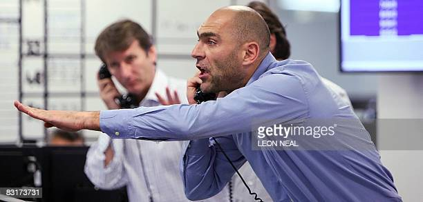 Brokers react to news of a 05% cut in the interest rate from the The Bank of England on ICAP's dealing floor in London on October 8 2008 The London...