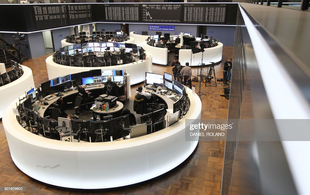 Brokers work at the stock exchange underneath displays showing the German stock market index DAX in Frankfurt, western Germany, on February 21, 2018. Deutsche Boerse February 21, 2018 addressed the media with the company's annual financial statement. / AFP PHOTO / Daniel ROLAND