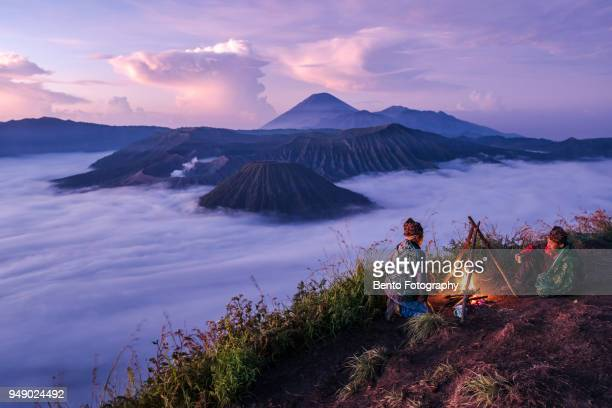 16-04-2018 : bromo tengger semeru national park, indonesia : 2 local indonesian doing campfire while sunrise with mt.bromo in background - bromo tengger semeru national park stock photos and pictures