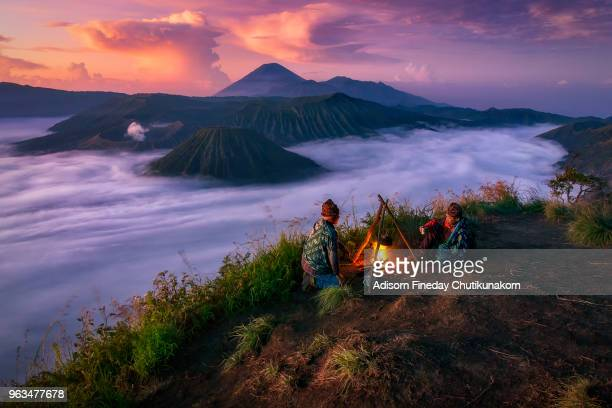 16-04-2018 : bromo tengger semeru national park, indonesia :2local indonesian people doing campfire during sunrise with mt.bromo in background - bromo tengger semeru national park stock photos and pictures