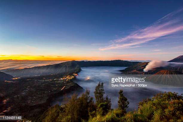 bromo volcano with sunrise sky background and foggy village - east java province stock pictures, royalty-free photos & images