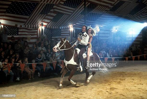 'Bronco' Billy McCoy played by Clint Eastwood on horseback with his assistant Antoinette Lily during a performance at a traveling circus in a scene...