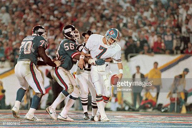 Bronco Quarterback John Elway looks like a rag doll 1/25 in hands of Giant linebacker Lawrence Taylor in 4th quarter end zone play the ref is...