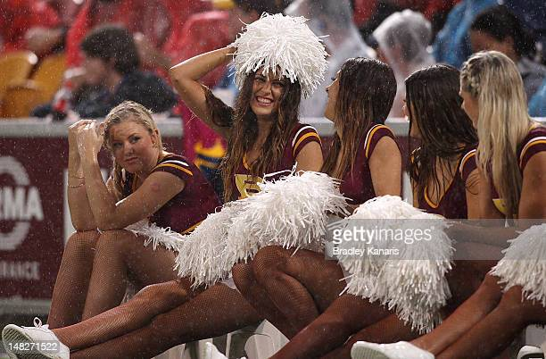 Broncos cheerleaders share a laugh in wet conditions during the NRL Round 19 game between the Brisbane Broncos and the New Zealand Warriors at...
