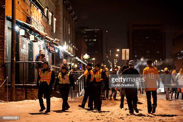 Broncos fans spill out of the bars as members of the Denver police department patrol in groups on foot after the conclusion of Super Bowl XLVIII in...