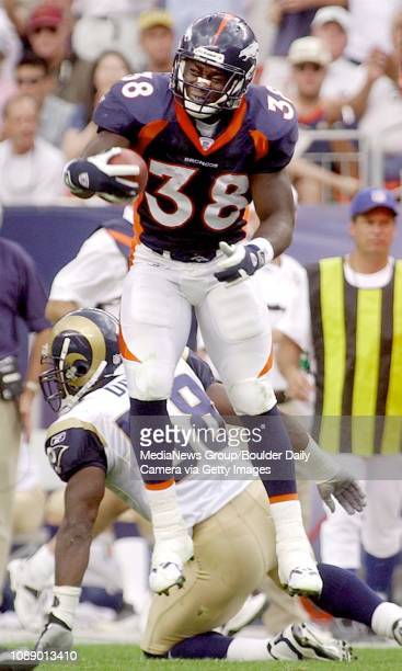 Broncos' tailback Mike Anderson celebrates a catch from QB Brian Griese in the second half as Ram's Don Davis gets off the grass at Invesco Field at...