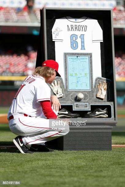 Bronson Arroyo of the Cincinnati Reds looks at shadow box made with his jersey batting gloves cleats ball and score card from the last game that he...