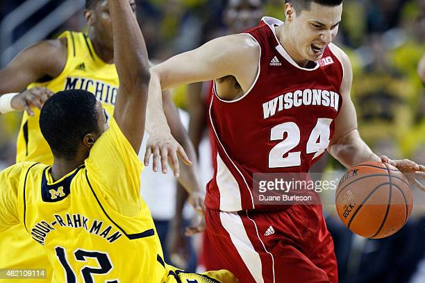 Bronson Koenig of the Wisconsin Badgers collides with MuhammadAli AbdurRahkman of the Michigan Wolverines while driving the ball up court during the...