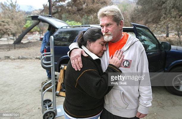 OCTOBER 12 2009––Bronwen Aker gets a hug from fire survivor Julius Goff while evacuating from her house in advance of an approaching storm in Big...