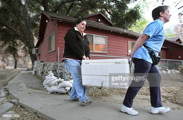 OCTOBER 12 2009––Bronwen Aker left receives help from friend Diane Wright while evacuating from her house for the winter in Big Tujunga Monday