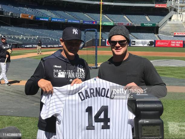 Jets quarterback Sam Darnold, right, holds up a Yankees jersey with his name on it as he stands with Yankees manager Aaron Boone at Yankee Stadium in...