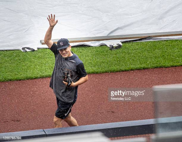 The New York Yankees' star pitcher Masahiro Tanaka waving to photographers after warning up in the rain during practice at Yankee Stadium in the...