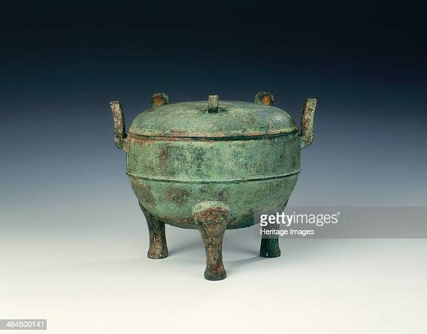Bronze covered ding, late Spring and Autumn period, China, 5th century BC. A large covered bronze ding with body decorated with two bands of...