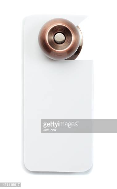 A bronze doorknob with blank white door sign