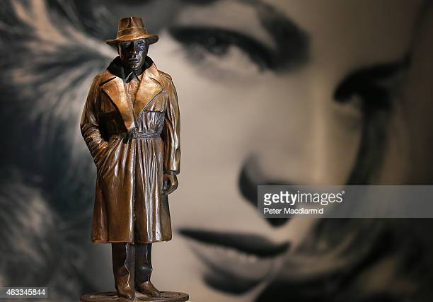 Bronze figure of Humphrey Bogart owned by Lauren Bacall is displayed in front of a photograph of the actress at Bonhams auctioneers on February 13,...