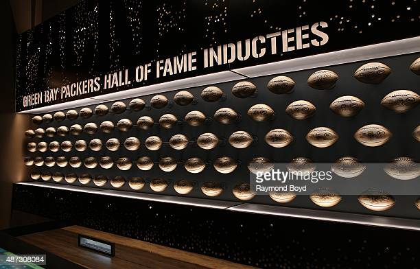 Bronze footballs honoring former Green Bay Packers football players are on display inside the Green Bay Packers 'Hall Of Fame' inductees room inside...