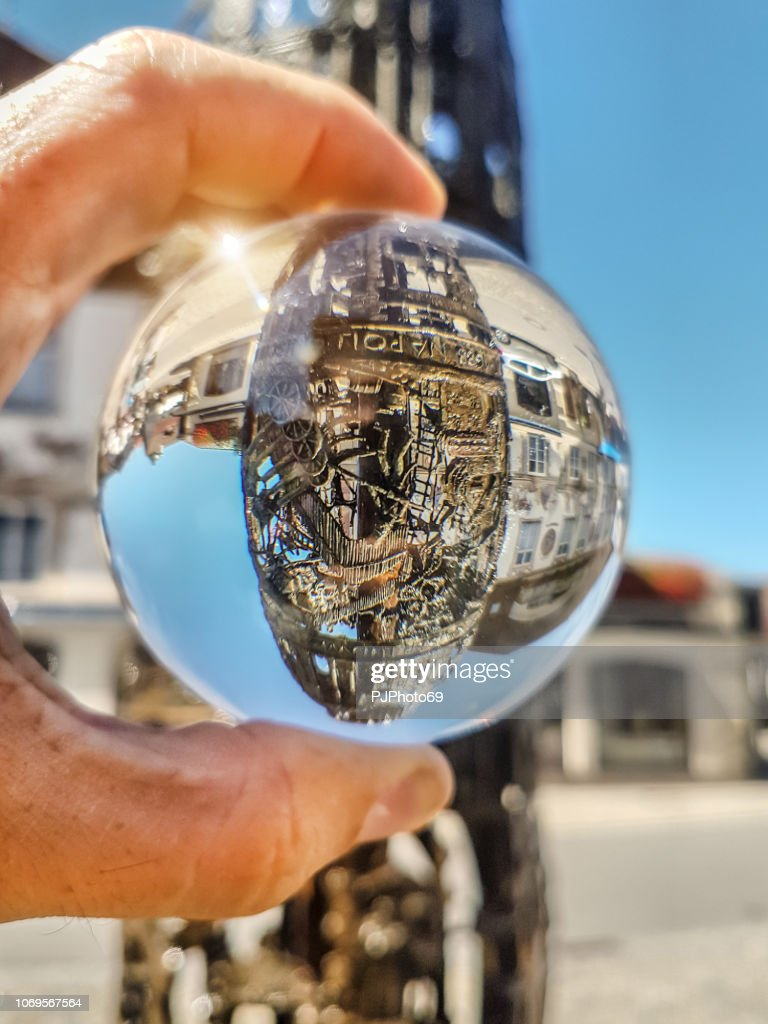 Bronze funtain in Oberammergau watched through lensball - Germany : Foto stock
