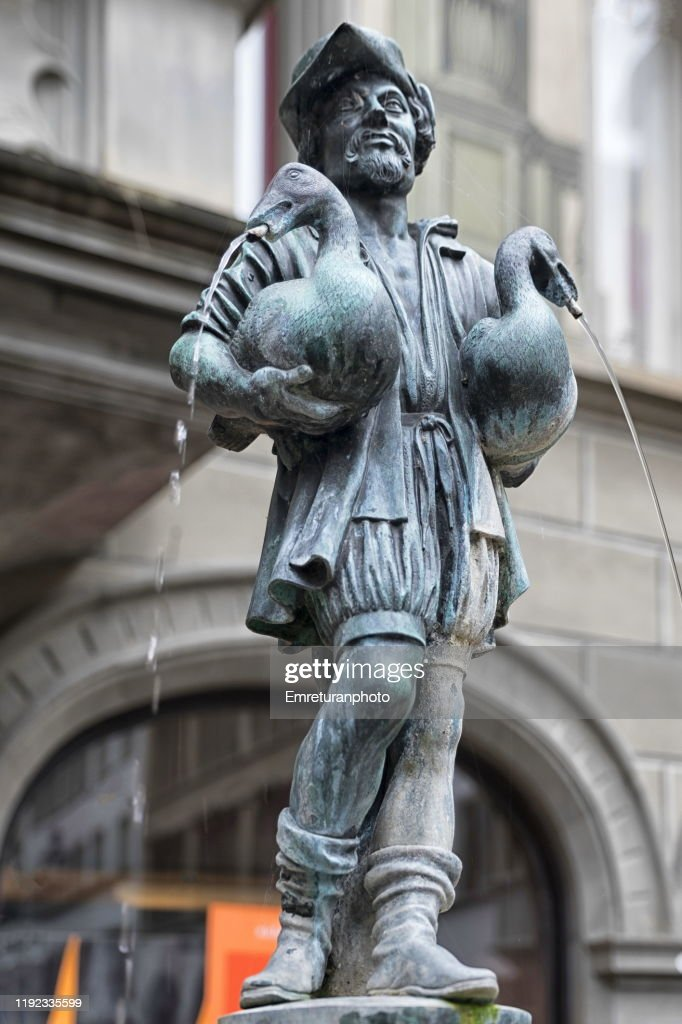 Bronze man holding two geese fountain,Lucerne. : Stock Photo
