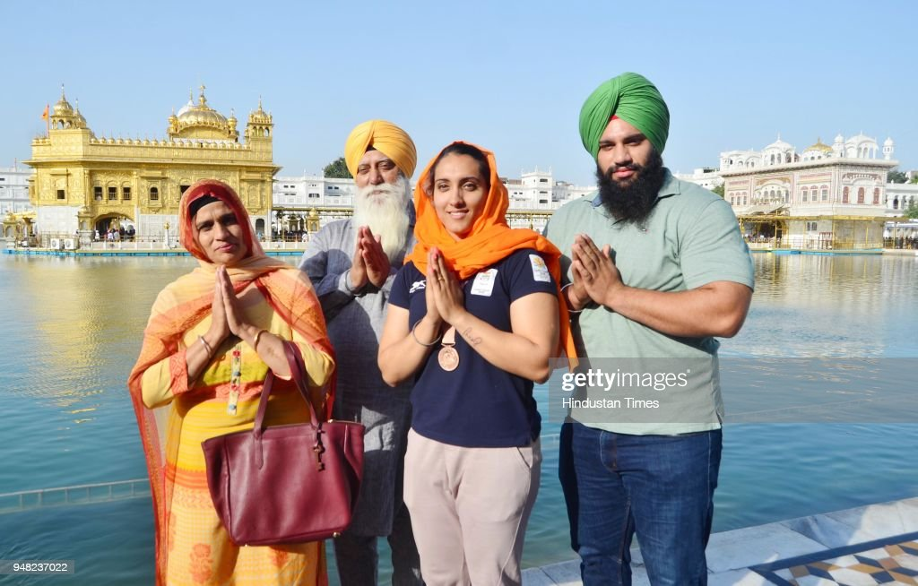Bronze medal winner Discus Thrower Navjeet Kaur Dhillon with her mother Kuldeep Kaur father Jaspal Singh brother Jasdeep Singh paying obeisance at...