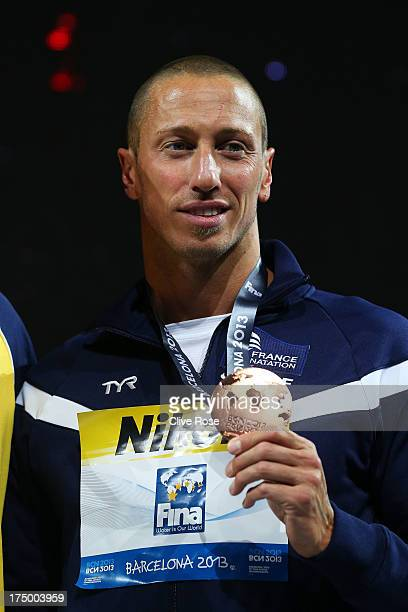 Bronze medal winner Frederick Bousquet of France celebrates on the podium after the Swimming Men's 50m Butterfly Final on day ten of the 15th FINA...
