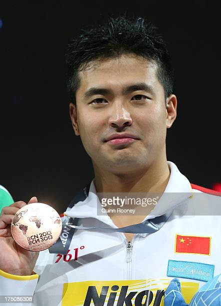 Bronze medal winner Peng Wu of China celebrates on the podium after the Swimming Men's 200m Butterfly Final on day twelve of the 15th FINA World...