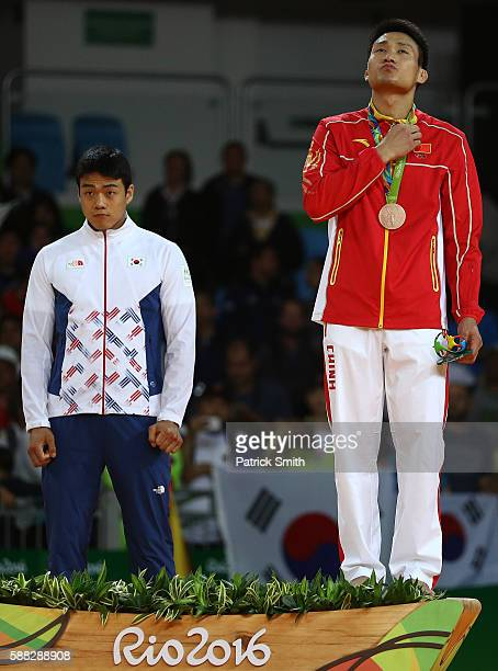 Bronze medalist A Donghan Gwak of Korea and bronze medalist B Xunzhao Cheng of China stand on the podium during the medal ceremony for the Men's 90kg...