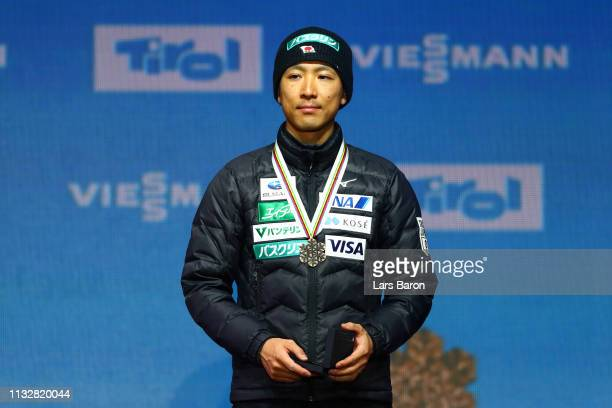 Bronze medalist Akito Watabe of Japan celebrates on the podium after the Men's Nordic Combined Individual Gundersen 10km during the medal ceremony...