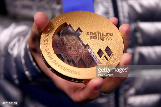 Bronze medalist Alex Deibold of the United States celebrates during the medal ceremony for the Men's Snowboard Cross on day 11 of the Sochi 2014...