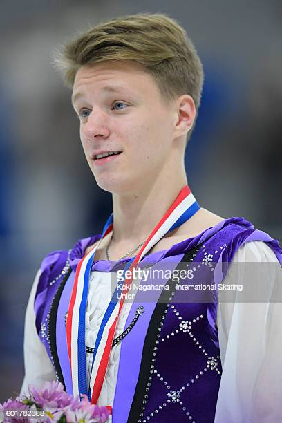 Bronze medalist Alexey Erokhov of Russia poses for photographs after the men's free program during the ISU Junior Grand Prix of Figure Skating...