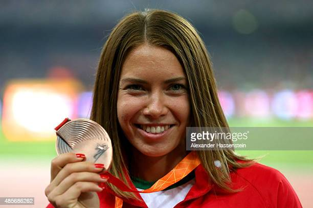 Bronze medalist Alina Talay of Belarus poses on the podium during the medal ceremony for the Women's 100 metres final during day eight of the 15th...