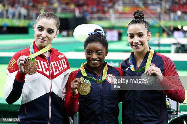 Bronze medalist Aliya Mustafina of Russia gold medalist Simone Biles of the United States and silver medalist Alexandra Raisman of the United States...