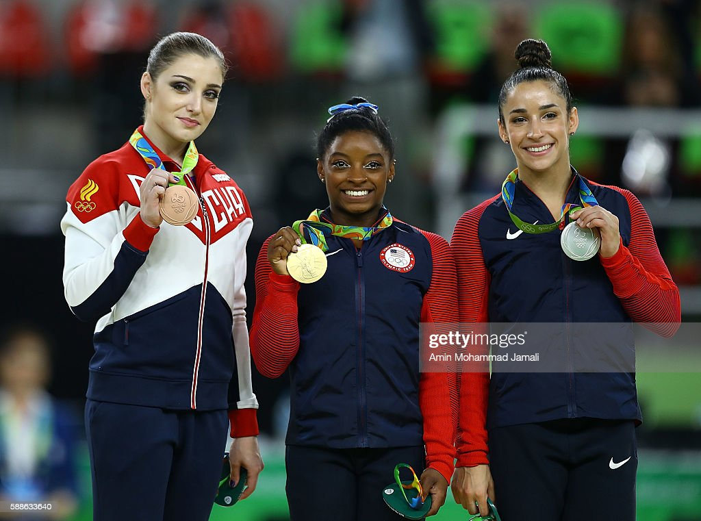 Bronze medalist Aliya Mustafina of Russia, gold medalist Simone Biles of the United States and silver medalist Alexandra Raisman of the United States pose for photographs on the podium at the medal ceremony for the Women's Individual All Around on Day 6 of the 2016 Rio Olympics at Rio Olympic Arena on August 11, 2016 in Rio de Janeiro, Brazil.